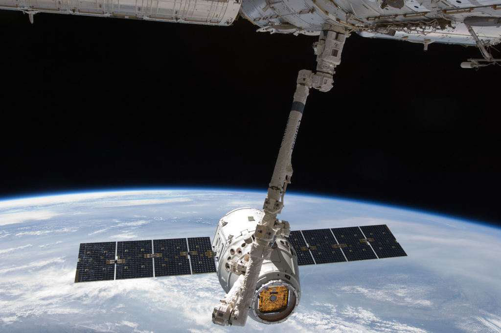 The SpaceX Dragon capsule in the grip of the robotic arm of the International Space Station during a May 2012 test run. A fully-stocked Dragon blasted off from Cape Canaveral and docked with the station Wednesday.