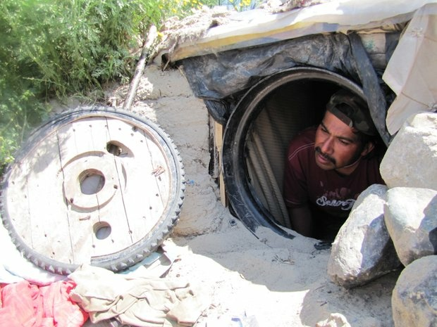Jesus, a deportee, peeks out of the hole he dug into a bank of the Tijuana river. These types of gopher hole-like homes pock the river's banks, built by deportees with no place else to go.