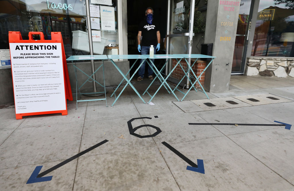 A restaurant worker wears a face covering and gloves for handling takeout orders, with social distancing markings on the pavement and instructions posted, amid the coronavirus pandemic on April 5, 2020 in Los Angeles, California.