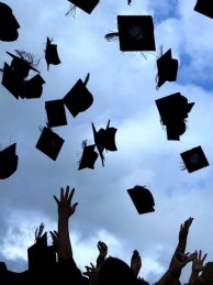Students throw their mortarboards in the air during their college graduation.