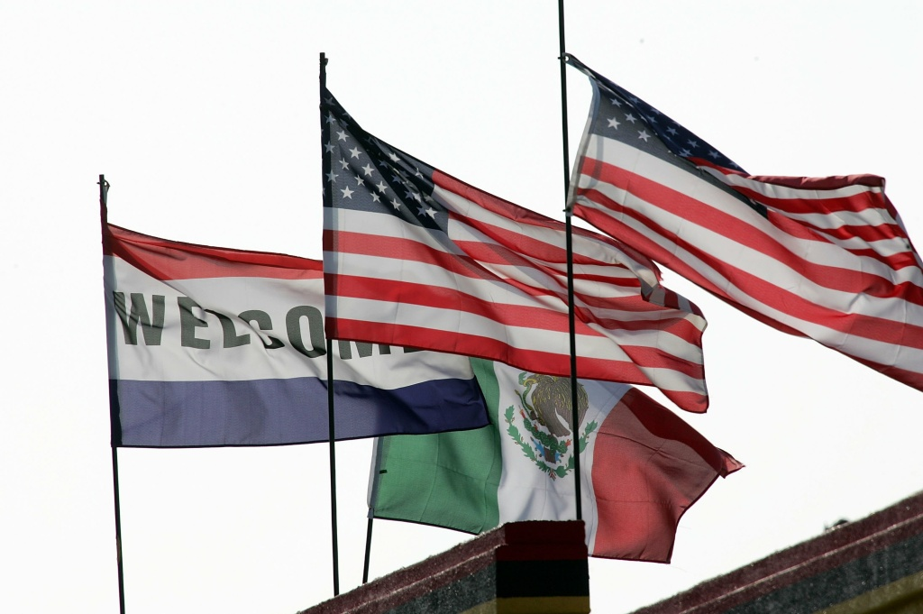 A welcome flag is flanked by the flags of the U.S. and Mexico on top of a building May 16, 2006 in the Los Angeles-area city of Maywood, California.