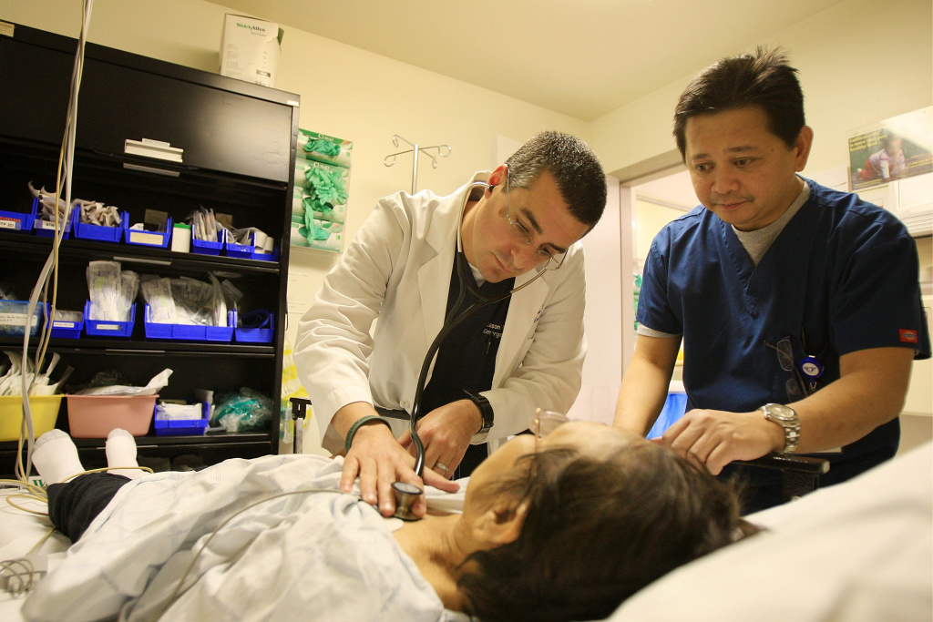 Dr. Jason Greenspan (L) and emergency room nurse Junizar Manansala care for a patient in the ER of Mission Community Hospital.