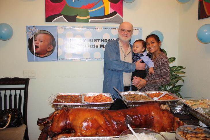 David, Isaac, and Ivy Haldane with lechon, a traditional pork dish, at Isaac's first birthday.