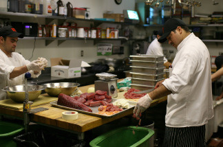 A cook drops fish skin and fat into a recycling container at MoMo's restaurant in San Francisco, California.