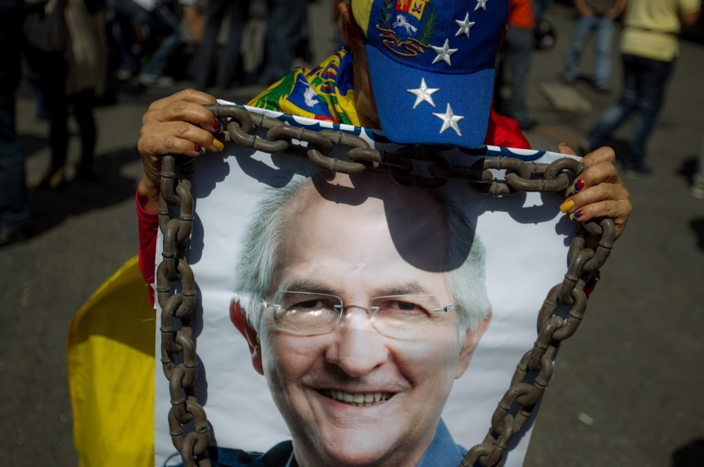 A woman holds up a blanket with the portrait of Caracas Mayor Antonio Ledezma during a demonstration on Feb. 20 to protest his detention. He was arrested on charges of planning a coup, which he denies. He is one of three opposition mayors who have been jailed; more than 30 face criminal charges.