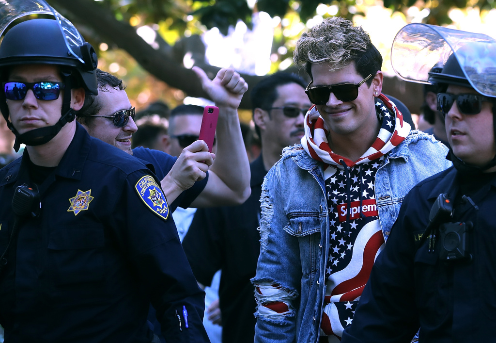 BERKELEY, CA - SEPTEMBER 24:  Right wing commentator Milo Yiannopoulos is escorted by police officers after he spoke during a free speech rally at U.C. Berkeley on September 24, 2017 in Berkeley, California. Hundreds of protesters came out to support and demonstrate against Milo Yiannopoulos as he held a free speech rally at U.C. Berkeley.  (Photo by Justin Sullivan/Getty Images)
