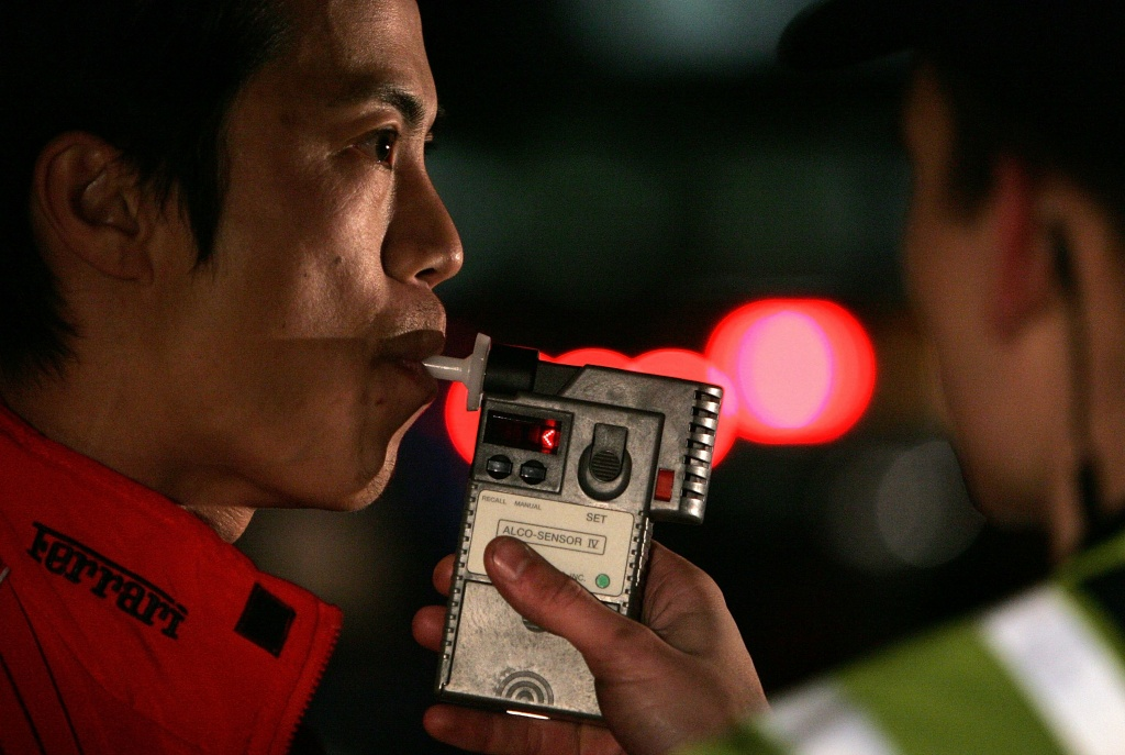 A man blows into a breathalizer during a field sobriety test after he was stopped by San Bruno Police officers at a DUI checkpoint in San Bruno, California.