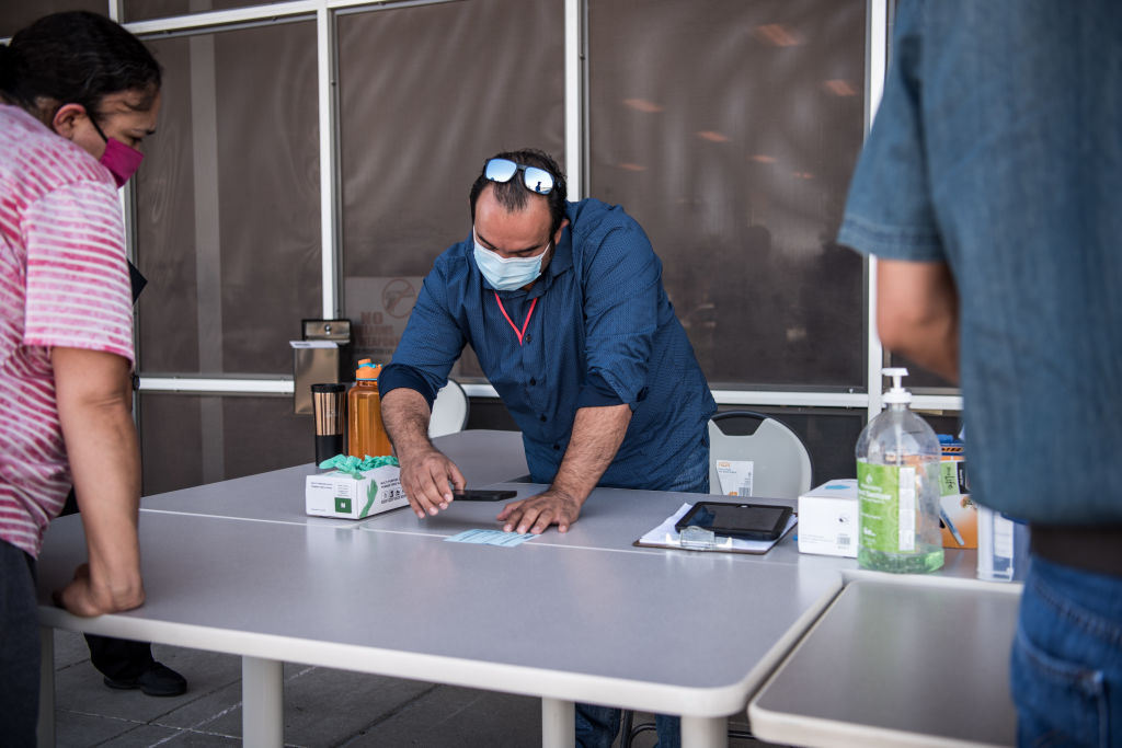 Zeke Salazar gives job search information to people on the sidewalk outside the Workforce Solutions Borderplex North Loop Center on July 2, 2020 in El Paso, Texas.