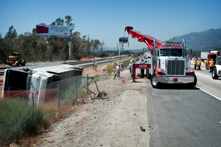 Tow trucks are used to remove pieces of a fence damaged during the crash. More than 50 were injured when a charter bus overturned on the 210 East in Irwindale on Thursday morning, Aug. 22.