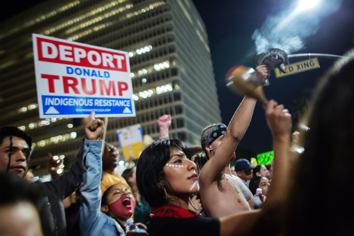 Demonstrators hold up placards a day after Donald Trump's victory, during a rally outside Los Angeles City Hall.