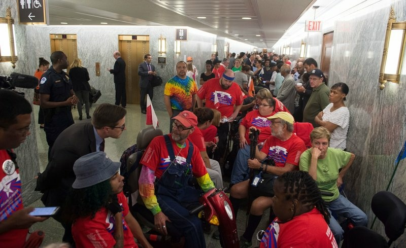 Activists and members of the public wait for a Senate Committee on Finance hearing on the latest GOP health care proposal on Capitol Hill on Monday. Once inside the hearing, activists began chanting and temporarily suspended the hearing.