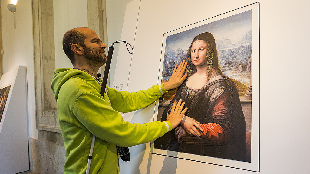 A blind visitor to Spain's Prado Museum runs his fingers across a 3-D copy of the