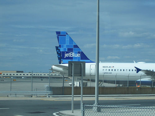 Two JetBlue planes at a gate.