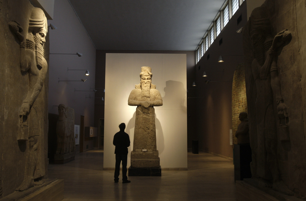 File: In this Nov. 24, 2009 file photo, a journalist looks at an Assyrian statue, center, in front of  two Assyrian human-headed winged bulls at Iraq's national museum, in Baghdad.  Islamic State militants