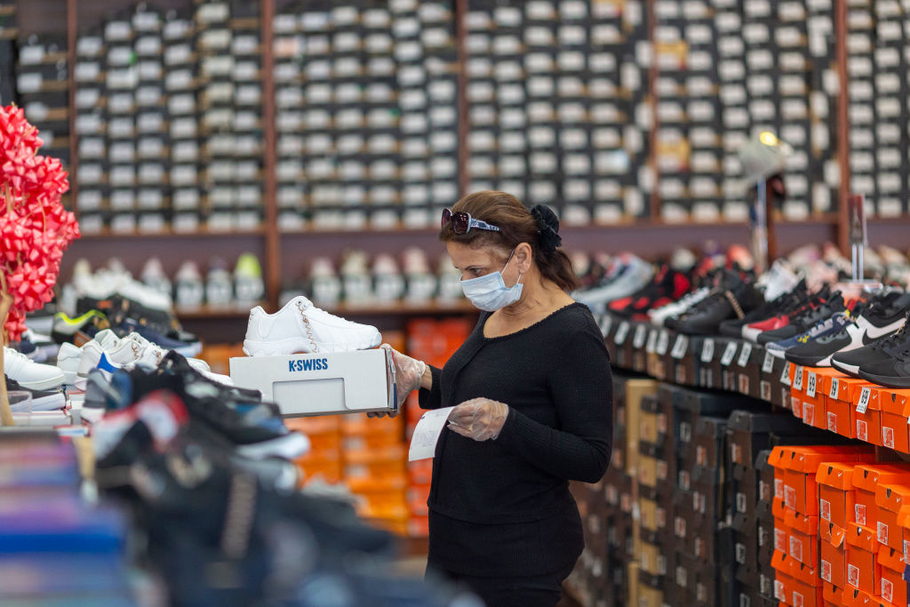 An employee stocks merchandise at a Shoe City store as Los Angeles County retail businesses reopen while the COVID-19 pandemic continues on May 27, 2020 in Glendale, California.