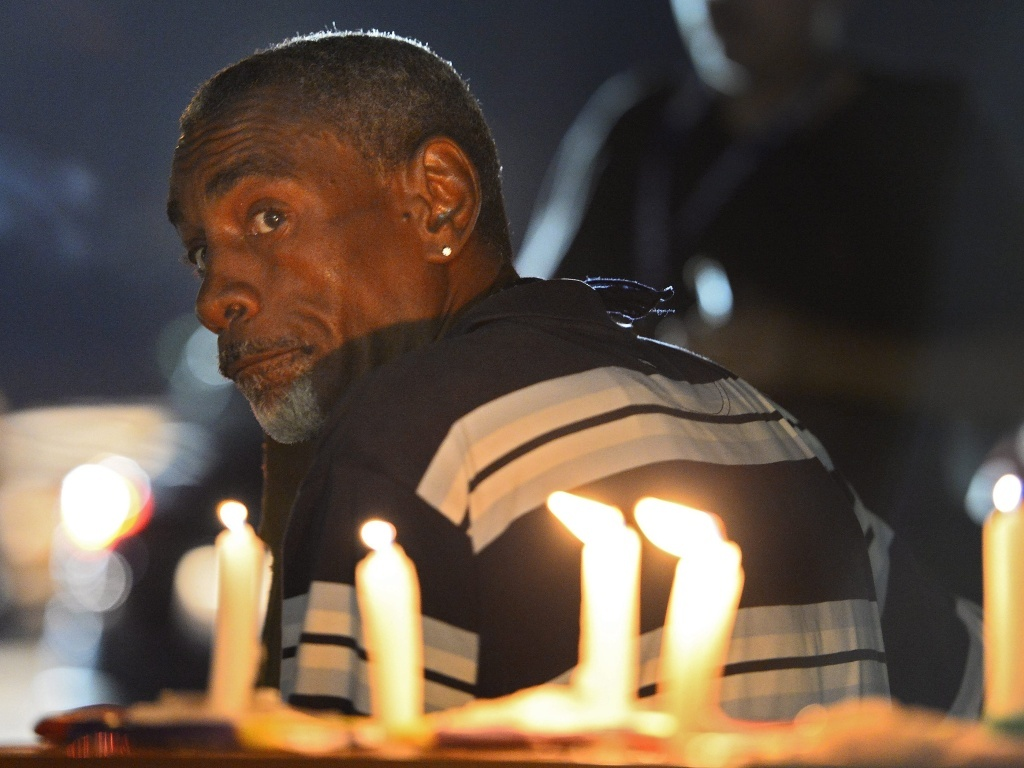 A demonstrator protesting the shooting death of Michael Brown in Ferguson, Missouri, Wednesday night. It was a night of relative calm after days of unrest.