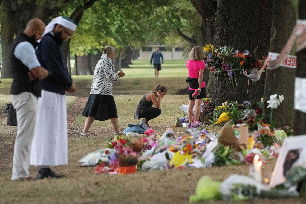 People on Tuesday stand next to floral tributes placed across the road from the Al Noor Mosque in Christchurch, New Zealand, where dozens of worshippers were gunned down last week.