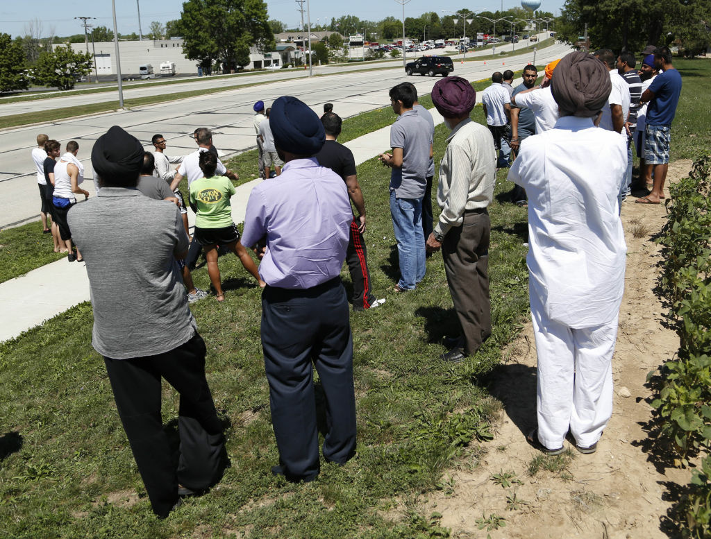 Bystanders look on as SWAT officers surround the Sikh Temple of Wisconsin where at least one gunman stormed a mass and opened fire August, 5, 2012 Oak Creek, Wisconsin. At least six people were killed when a shooter, who was shot dead by a police officer, opened fire on congregants in the Milwaukee suburb.