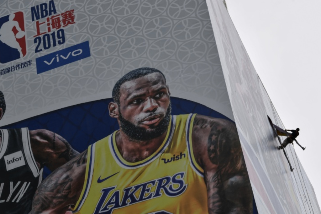 A worker removes a promotional banner from a building for the NBA October 10 preseason game in China between the Brooklyn Nets and the Los Angeles Lakers in Shanghai.