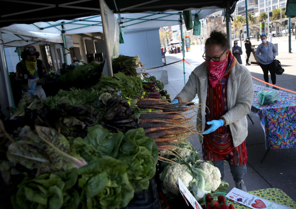 A worker picks vegetables for a customer during the Ferry Plaza Farmers Market  on April 21, 2020 in San Francisco, California.