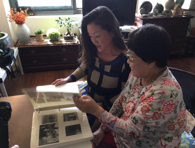 Jennifer Kang Erwood, left, and her mother, Kyung Kang, go through a family photo album. The family came to the United States after Kang was sponsored by her sister, who had married a U.S. soldier.