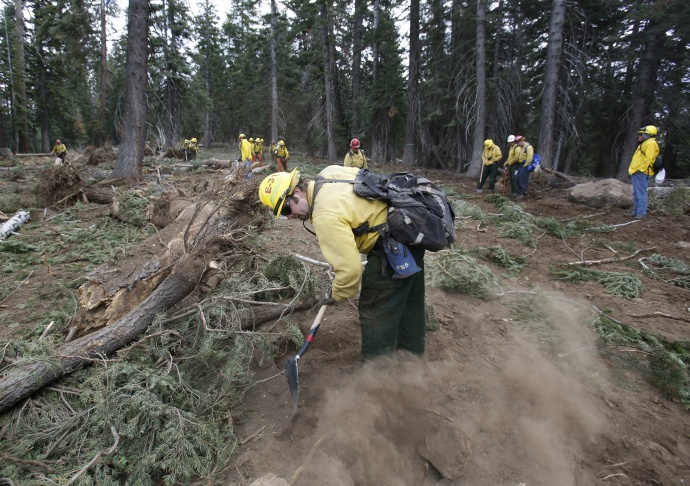 In this photo taken Thursday, Sept. 25, 2013 Scott Small, and other National Forest Service crew members work to restore terrain that was bulldozed for a firebreak in the battle against Rim Fire on a nordic ski trail along Dodge Ridge in the Stanislaus National Forest, near Tuolumne City, Calif. Just three weeks after flames of the Rim Fire consumed an estimated 30,000 acres of forest land, man and nature work to repair the forest.