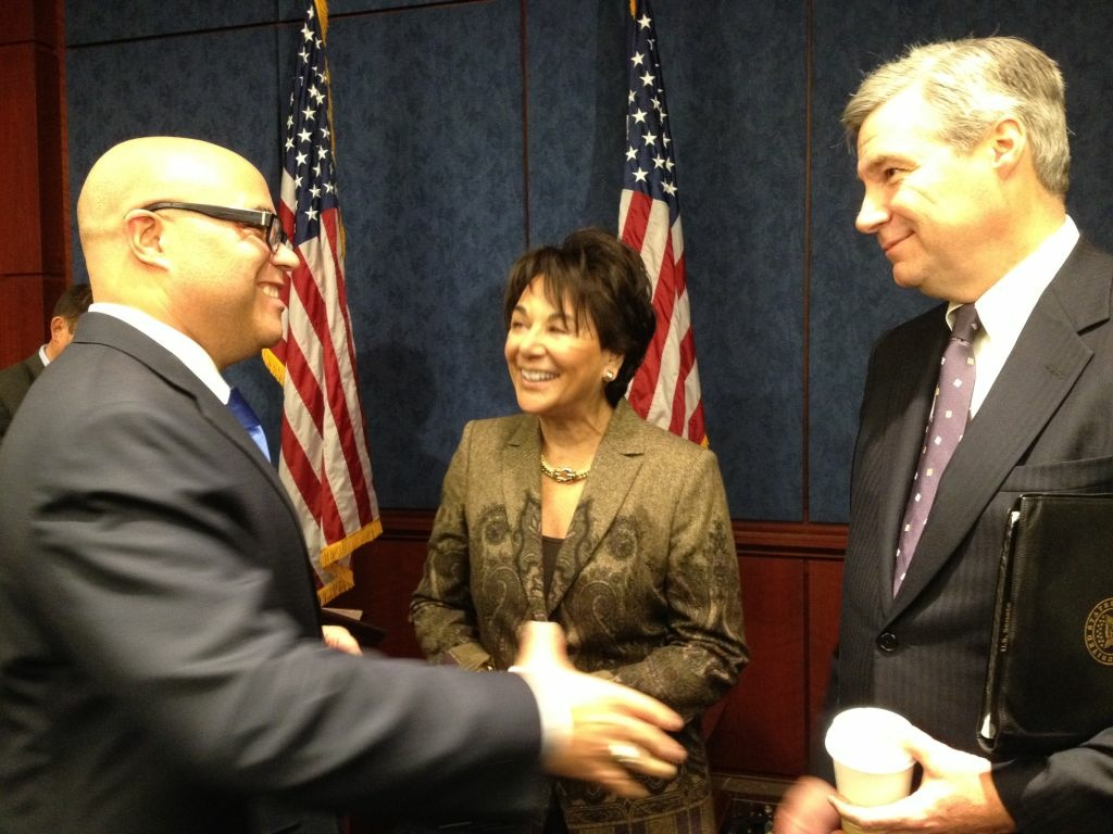 Former FCC Chair Michael Powell, left, congratulates Rep. Anna Eshoo and Sen. Sheldon Whitehouse on their bill, which regulates the volume of TV commercials.