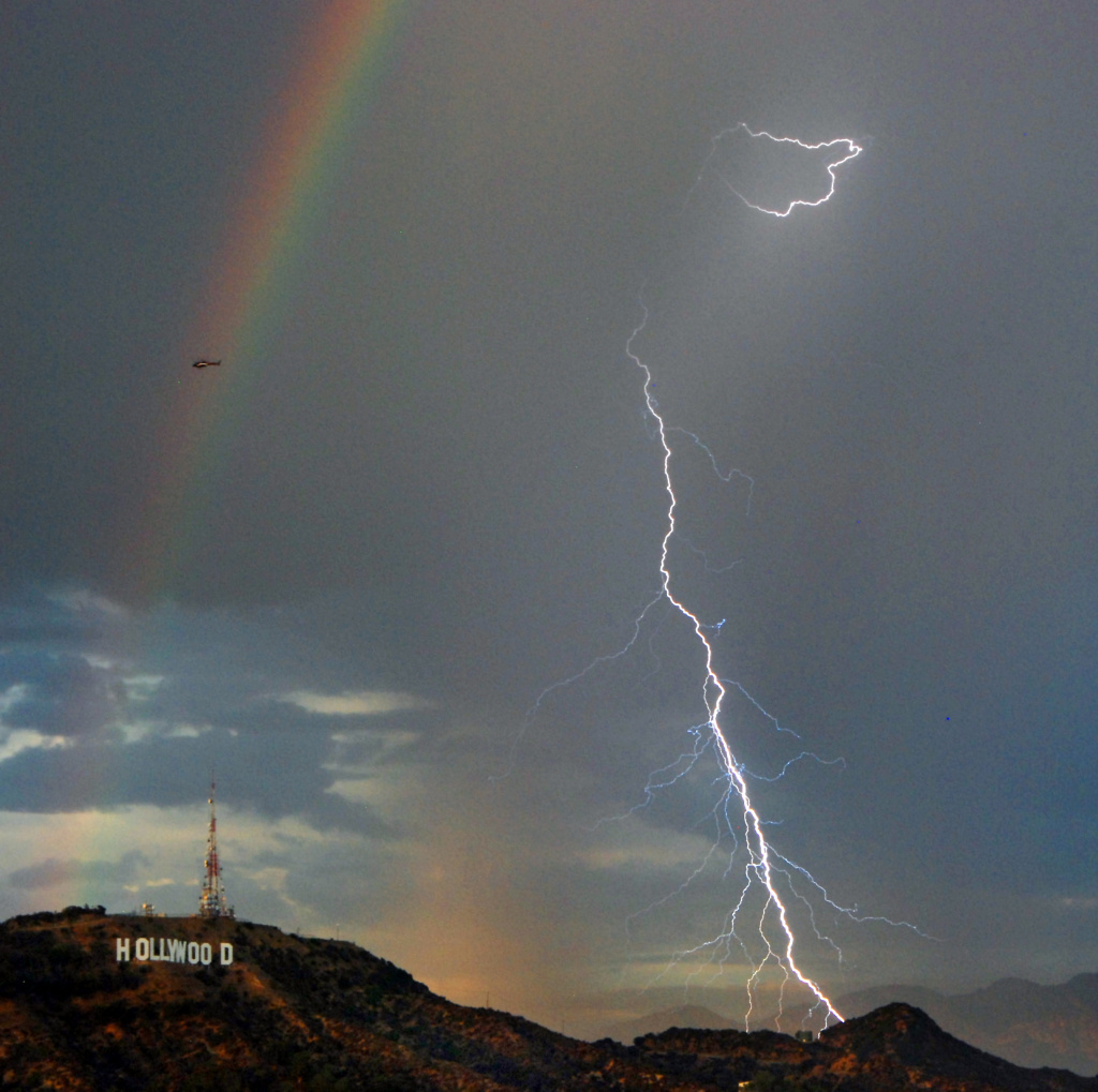 A rainbow and bolts of lightening are shown next to the Hollywood sign Wednesday Sept. 29, 2010 in Los Angeles. Days of historic heat in Southern California are ending with scattered thunderstorms and lightning strikes that raise the risk of wildfires in the region. (AP Photo/Mike Meadows)