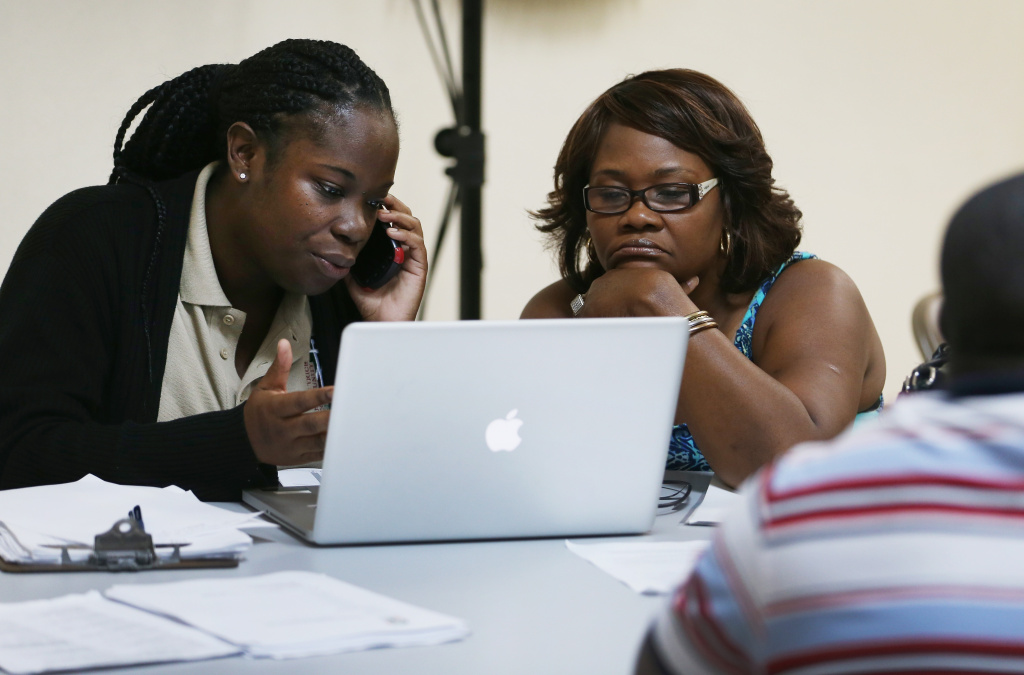Myrlene Charles (L), a Certified Application Counselor at the Jesse Trice Community Health Center, takes down information from Farah Smith as she signs up for health insurance under the Affordable Care Act at the Mount Sinai Missionary Baptist Church on March 29, 2014 in Miami, Florida. In two days, March 31st, the enrollment period for people wanting to get health care coverage this year comes to an end.