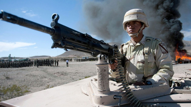 A Mexican soldier stands guard as a haul of marijuana and cocaine are incinerated in the background in November 2009.