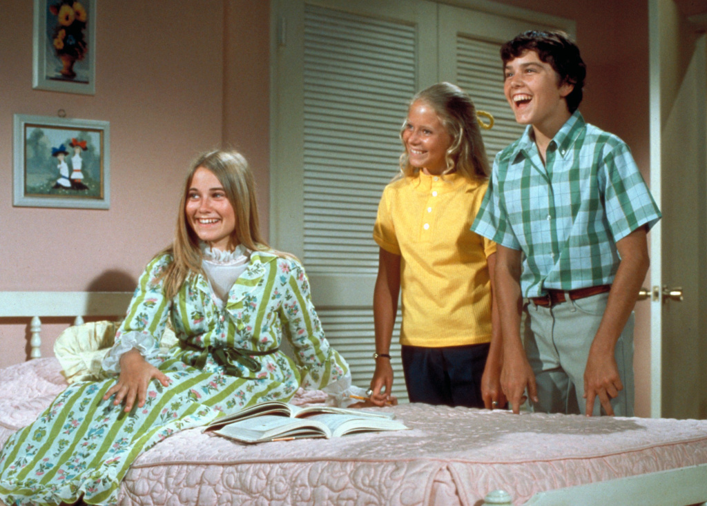 The Brady Bunch Circa 1970, with Marcia seated in front. In one episode of the show from 1969, the sisters and brothers all stay home from school with the measles.