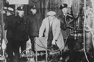 Detroit police inspecting equipment found in a clandestine underground brewery during the prohibition era.