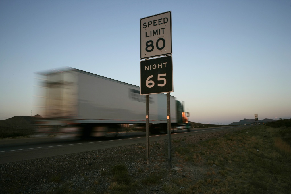 Trucks pass by a sign indicating an 80 mph speed limit ion Interstate 10 outside of the West Texas town of El Paso.
