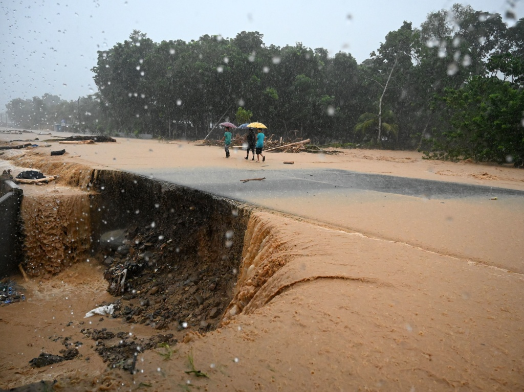 Men walk along a flooded road Wednesday in Toyos, Honduras, after heavy rains from Eta caused a river to overflow.