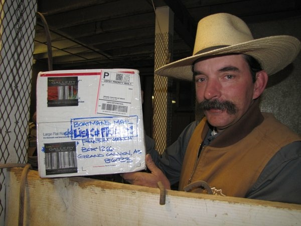 John Berry is in charge of the mules on the south rim of the Grand Canyon. He holds up a package for a boatman. Packages will no longer be delivered after April 15.