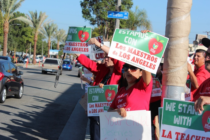 Members and supporters of United Teachers Los Angeles, the union representing L.A. Unified School District teachers, wave signs during a demonstration along Firestone Boulevard in South Gate on Weds., Oct. 24, 2018. (Photo by Kyle Stokes/KPCC)