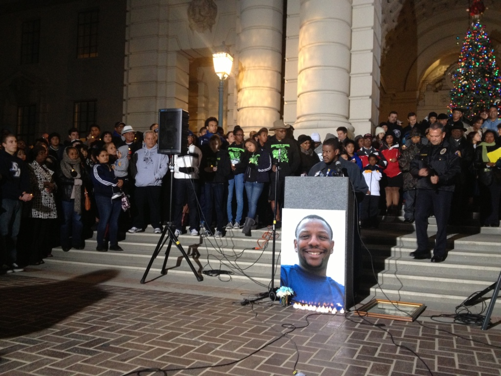 About 400 people stand behind a photo of Victor McClinton at Pasadena City Hall on Dec. 27, 2012. It was part of a memorial to honor the youth sports mentor who was killed on Christmas 2012.