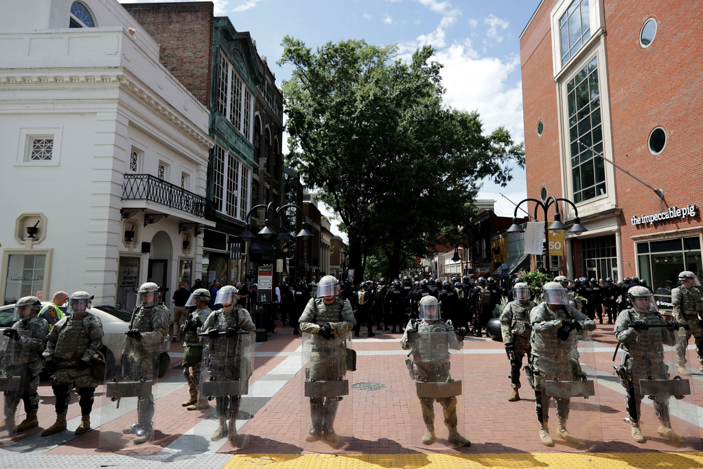 Members of the Virginia National Guard wear body armor and carry riot shields while standing guard on the pedestrian mall following violence at the United the Right rally August 12, 2017 in Charlottesville, Virginia.