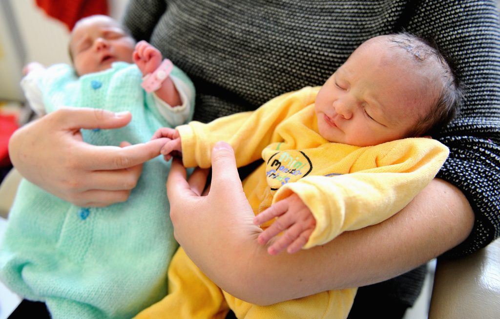 September 17, 2013: A mother holds her twin daughters. Parents are increasingly embracing gender-neutral names for their children.
