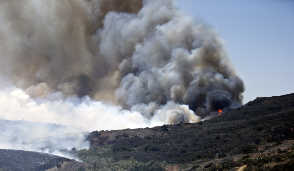 In this file photo, billowing smoke rises from flames as firefighters begin the trek up the hills to battle a wildfire on Tuesday, May 13, 2014, in San Diego. Triple digit heat is expected across the warmest portions of the valleys, foothills and lower mountains through Tuesday, raising the fire danger for much of Southern California.