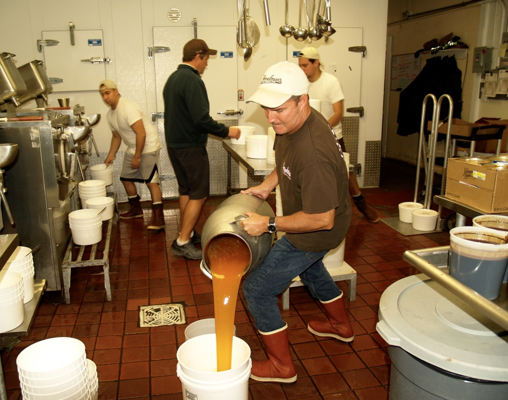 Chris Fosselman, forefront, pours salted caramel into a bucket to use in a mixer. John, center back, coordinates the hand packing with other staff members.