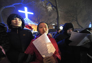 Chinese worshippers wait to enter a Catholic church for Christmas mass in Beijing on December 24, 2009.