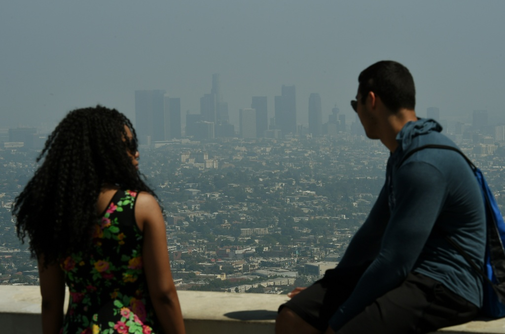 Tourists at the Griffith Observatory observation deck look out at the Los Angeles city skyline as heavy smog shrouds the city on May 31, 2015.