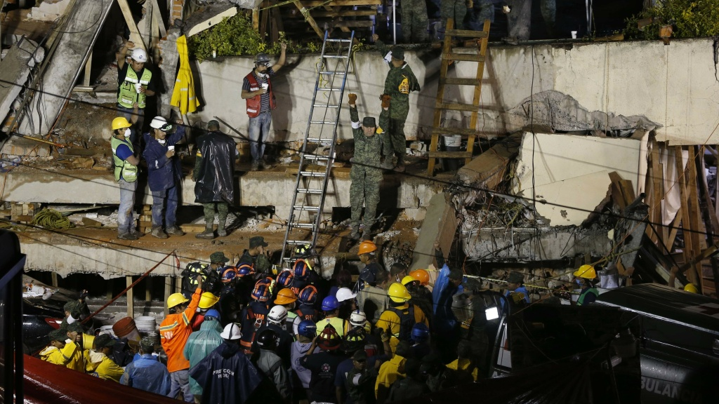 Rescue personnel work at the scene of Enrique Rebsamen School, which collapsed when an earthquake struck on Tuesday. Reports said workers were looking for a trapped little girl, but authorities now say it may be an adult.