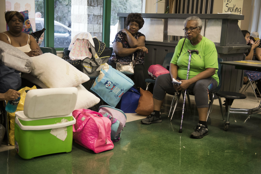 A group of women sit in the cafeteria awaiting room assignments at a shelter within the Pizzo Elementary School in Tampa, Florida on September 9, 2017.