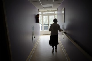 A woman, suffering from Alzheimer's disease, walks in a corridor.