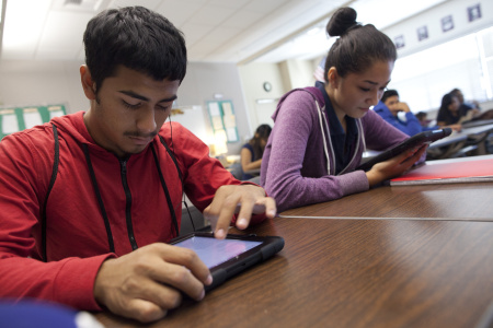 Brayan Aguilar, 17, and Yadira Aragon, 16, use iPads to read electronic books in a literacy class at Diego Rivera Learning Complex.