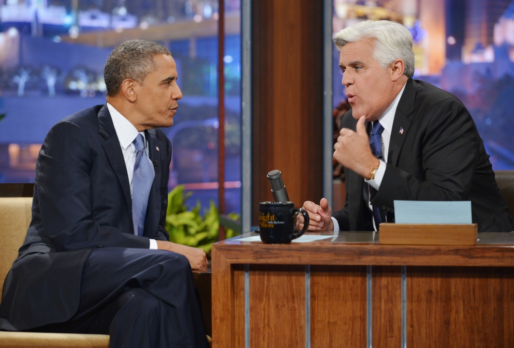 US President Barack Obama chats with host Jay Leno during a taping of The Tonight Show with Jay Leno at NBC Studios on August 6, 2013 in Burbank, California.