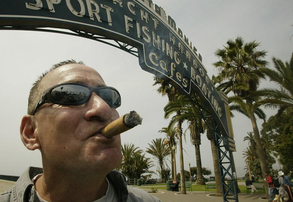 Chuck Rank, a tourist from Pennsylvania, smokes a cigar at the Santa Monica Pier in Santa Monica.