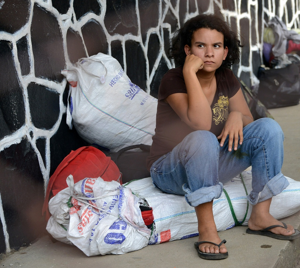 A young girl waits for her family upon arriving to San Pedro Sula, 240 kms north of Tegucigalpa, on July 2, 2014, after being deported from the US. Thousands of unaccompanied children, most of them from Central America, have trekked to the United States in recent months and now face deportation in what the United States has called a humanitarian crisis.